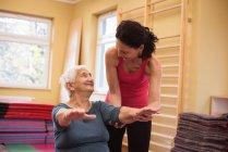 Femme thérapeute aide femme senior avec main d'exercice à la maison de soins infirmiers — Photo de stock