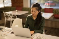 Female executive using laptop in cafeteria at office — Stock Photo