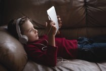 Boy using digital tablet with headphones in living room at home — Stock Photo