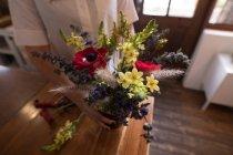 Sezione centrale della donna che tiene il vaso di fiori a casa — Foto stock
