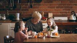 Mère et les enfants prennent le petit déjeuner à table dans la cuisine — Photo de stock
