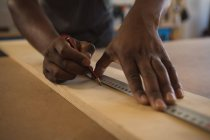 Mid section of carpenter measuring wooden plank with scale in workshop — Stock Photo