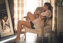 Femme assise sur une chaise tout en prenant un café à la maison . — Photo de stock