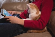 Boy using digital tablet in living room with his cat at home — Stock Photo