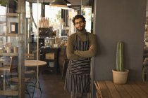 Portrait of waiter standing with arms crossed in coffee shop — Stock Photo