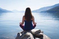 Femme de pratiquer l'yoga sur la roche près de bord de mer — Photo de stock