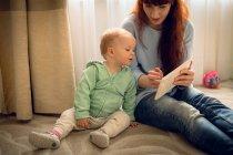 Mère montrant à sa petite fille une tablette numérique à la maison — Photo de stock