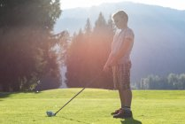 Side view of boy hitting golf shot in the course — Stock Photo