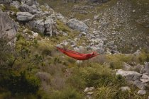 Hiker relaxing in hammock on a sunny day — Stock Photo
