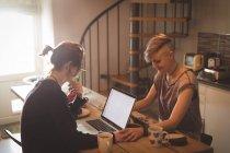 Pareja lesbiana usando laptop y tomándose de la mano en casa . - foto de stock
