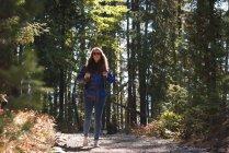 Жіночий мандрівного, стоячи з рюкзак в лісі на сонячний день — стокове фото