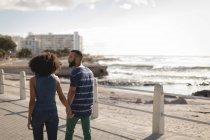 Couple marchant main dans la main sur le trottoir par une journée ensoleillée — Photo de stock