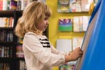 Ragazza che scrive sulla lavagna in libreria — Foto stock