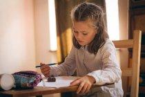 Внимательная маленькая девочка делает домашнее задание — стоковое фото