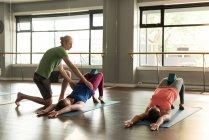 Тренер, помогающий женщинам практиковать йогу в фитнес-студии . — стоковое фото