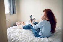 Матери и ребенка девушка принимая selfie с мобильного телефона в спальне дома — стоковое фото