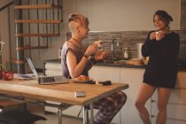 Young women talking with cups of coffee in kitchen at home. — Stock Photo