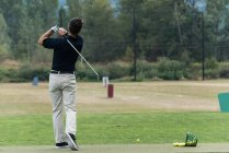 Man performing a golf swing in the golf course — Stock Photo