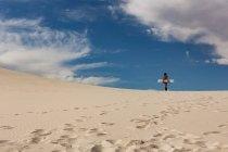 Rückansicht des Frau mit Sandboard stehen in der Wüste an einem sonnigen Tag — Stockfoto