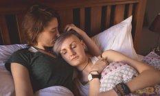 Coppia lesbica coccole sul letto in camera da letto a casa . — Foto stock