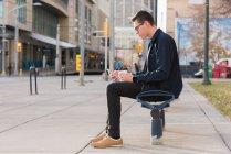 Homem usando o celular enquanto tomando café na rua — Fotografia de Stock