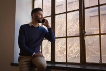Geschäftsmann telefoniert in Bürofenster mit Handy. — Stockfoto
