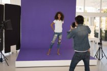 Professional Photographer taking picture of model in studio — Stock Photo
