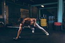 Мускулистый человек делает отжимания с гантелями в фитнес-студии — стоковое фото