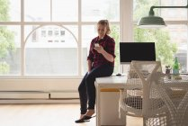 Weibliche Führungskraft mit Handy in das kreative Büro — Stockfoto