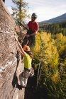 Determinata coppia salendo la montagna rocciosa — Foto stock