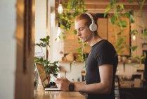 Человек прослушивания музыки на наушники во время мобильный телефон в кафе — стоковое фото