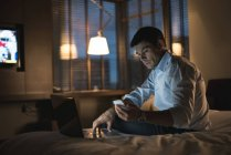 Businessman using laptop and mobile phone in bedroom at hotel — Stock Photo