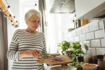 Senior woman adding cut onions to a bowl in the kitchen — Stock Photo