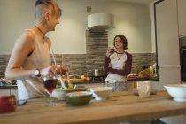 Молодые женщины смешивают салат и вино на кухне дома . — стоковое фото