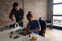Father and daughter repairing electric model car and circuit board in office. — Stock Photo