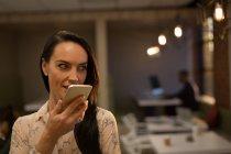 Executivo feminino falando no celular no escritório — Fotografia de Stock