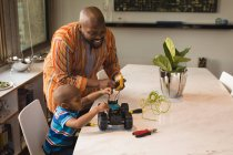 Father and son repairing electric car at home table. — Stock Photo