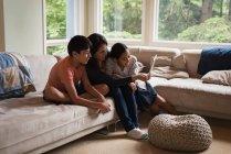 Мать и дети, имеющие видеозвонок на ноутбуке в гостиной дома — стоковое фото