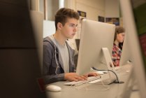 Teenage boy studying in computer classroom at university — Stock Photo