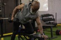Homem sênior determinado levantando com haltere no estúdio de fitness . — Fotografia de Stock