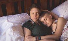 Pareja lesbiana abrazándose mientras duerme en la cama en el dormitorio en casa . - foto de stock