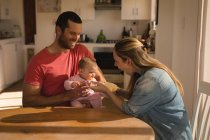 Happy parents feeding baby boy by table at home. — Stock Photo