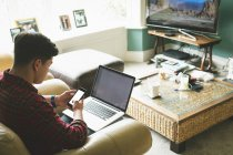 Man using laptop and mobile phone in living room at home. — Stock Photo