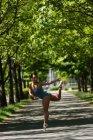 Молодая балетная танцовщица танцует на дороге — стоковое фото
