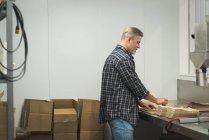 Человек, подготовке картонную коробку на фабрике — стоковое фото