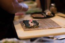Srotolato sushi tenuto su un tavolo in un ristorante — Foto stock