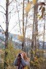 Красива жінка беручи малюнок осінній ліс з цифрової камери — стокове фото