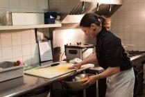 Mettre les légumes hachés dans le grand bol dans la cuisine de chef — Photo de stock