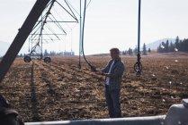 Фермер проверяет автоматизированную систему орошения в поле — стоковое фото