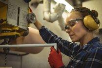 Arbeitnehmerin, die eine Maschine im Werk in Betrieb — Stockfoto